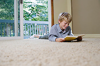 Young boy (5-6) lying on carpet reading book