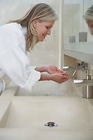 Mature woman in bathrobe washing face over sink profile