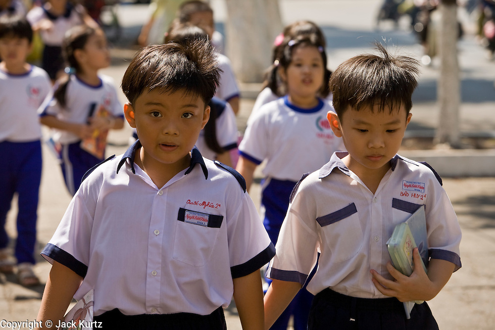 09 MARCH 2006 - HO CHI MINH CITY, VIETNAM: School boys in their elementary school uniforms walk down a street in Ho Chi Minh City (Saigon), Vietnam.   PHOTO BY JACK KURTZ
