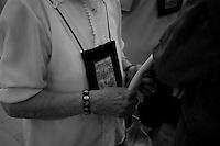 Questa fedele appartine al 3° ordine Carmelitano. Appartengono a quest'ordine solo le donne, e si riconoscono dallo stemma che portano esposto raffigurante la protettrice di Mesagne, la Madonna del Carmine. La foto è stata scattata nella chiesa dell'Arcangelo Michele durante la celebrazione della messa in onore della Santa Protrettrice, il 15-07-10
