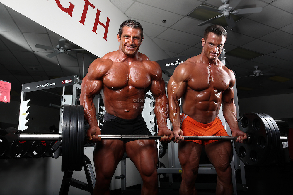 Bodybuilders Dan Decker and Brian Yersky working out together lifting weights.