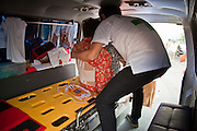 16 MAY 2010 - BANGKOK, THAILAND: A Thai woman who collapsed at an anti government barricade on Rama IV Road is put into an ambulance for transport to a hospital Sunday. (She was not shot.)  Thai troops and anti government protesters clashed on Rama IV Road again Sunday afternoon in a series of running battles. Troops fired into the air and unidentified snipers shot at pedestrians on the sidewalks. At one point Sunday the government said it was going to impose a curfew only to rescind the announcement hours later. The situation in Bangkok continues to deteriorate as protests spread beyond the area of the Red Shirts stage at Ratchaprasong Intersection. Many protests now involve people who have not been active in the Red Shirt protests and live in the vicinity of Khlong Toei slum and Rama IV Road. Red Shirt leaders have called for a cease fire, but the government indicated that it is going to go ahead with operations to isolate the Red Shirt camp and clear the streets.      PHOTO BY JACK KURTZ