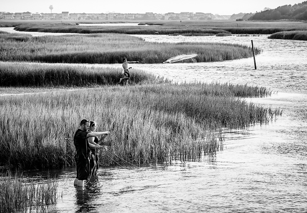 Crab fishermen in the foreground bait their trap, while the fisherman further back throws his minnow net into the marsh along the Intracostal Waterway near the Ferry Landing Park pier at Ocean Isle Beach, North Carolina.