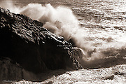 Storm waves crash over the headland at Cable Bay on West Anglesey.