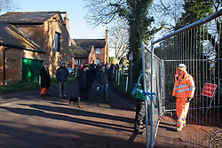Harefield, UK. 18 January, 2020. Activists from Extinction Rebellion, Stop HS2 and Save the Colne Valley walk down Dews Lane towards a public footpath leading to Stop HS2's Colne Valley wildlife protection camp which had been fenced off by enforcement agents acting for HS2. They are attending a three-day 'Stand for the Trees' event timed to coincide with tree felling work by HS2. The enforcement agents have been evicting Stop HS2 activists from the camp for the past week and a half. 108 ancient woodlands are set to be destroyed by the high-speed rail link.