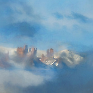 Castle shaped rock formation surrounded by fluffy clouds on a blue sky