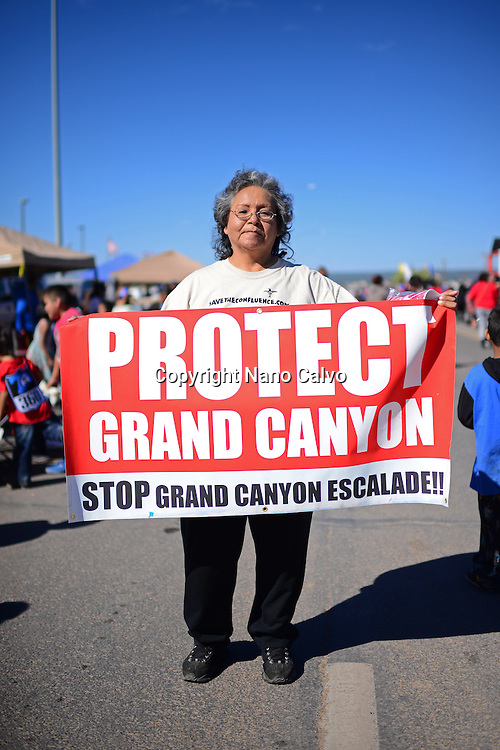 "Woman holds ""Protect Grand Canyon"" sign during morning parade at Navajo Nation Fair, a world-renowned event that showcases Navajo Agriculture, Fine Arts and Crafts, with the promotion and preservation of the Navajo heritage by providing cultural entertainment. Window Rock, Arizona."