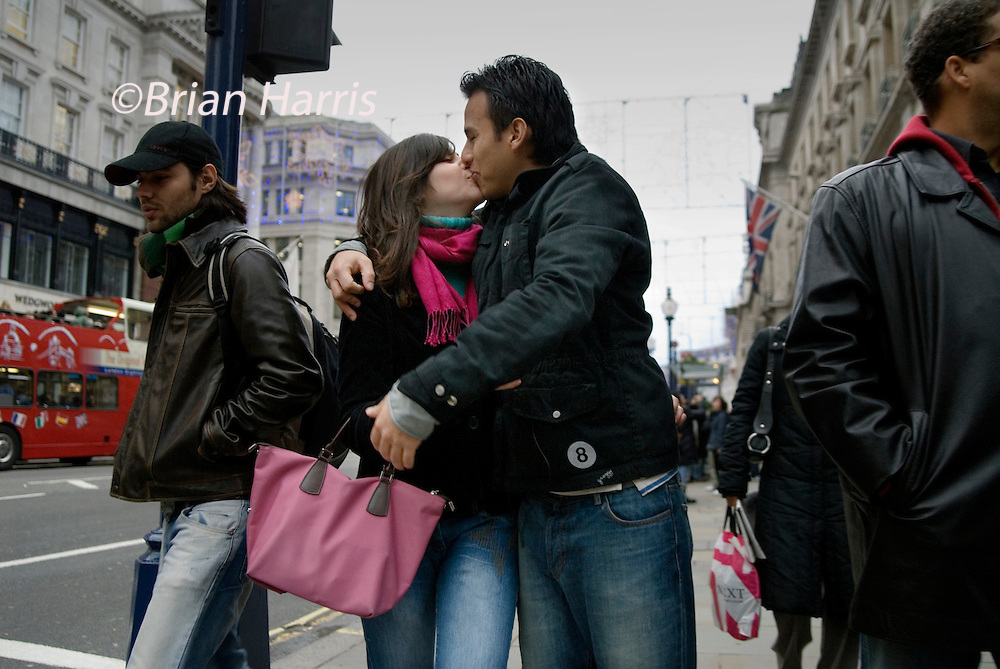 Kiss 16. Part of a series of images produced by the photographer while travelling  as a working photo-journalist on the subject of 'love'.<br /> A couple kiss on Regents Street, London while doing their Christmas shopping.2006.