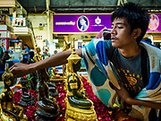 11 APRIL 2018 - BANGKOK, THAILAND: A man bathes Buddha statues in holy water to make merit at Hua Lamphong train station in Bangkok on the first day of the Songkran travel period. Songkran is the traditional Thai New Year and is one of the busiest travel periods of the year as Thais leave the capital and go back to their home provinces or resorts in tourist areas. Trains and busses are typically jammed the day before the three day Songkran holiday starts. The government has extended the official holiday period through Monday, 16 April because one day of the Songkran holiday fell on the weekend, giving many workers a five day holiday.     PHOTO BY JACK KURTZ