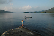 Girl on a island in the Adirondaks greets a family in a canoe paddling on the secluded lake.