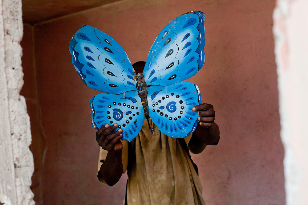 A man holds a butterfly found in the rubble of a former school on July 7, 2010 in Port-au-Prince, Haiti.