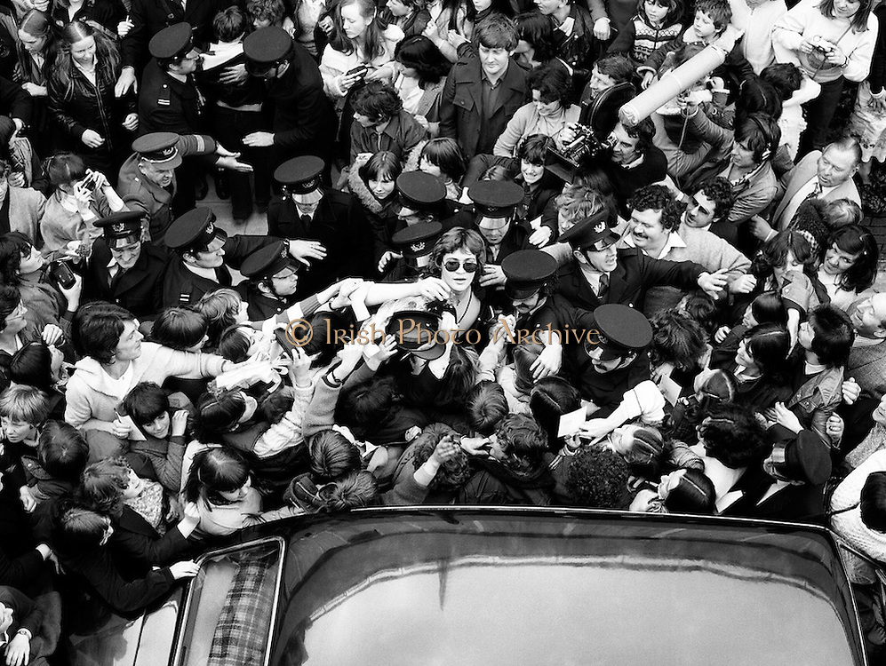 Johnny Logan (centre, dark glasses), protected by a strong guard of Airport Police, struggles to reach his car through a mob of teenagers at Dublin Airport, on arrival from victory at the Eurovision Song Contest in Holland.<br /> 21 April 1980