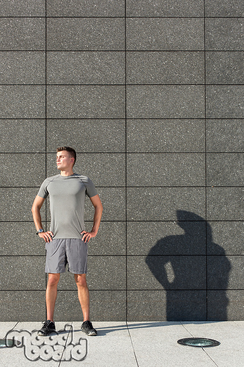 Determined jogger standing with hands on hips against tiled wall outdoors