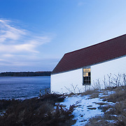 An abandoned, historic lifeguard hut sits along the Kennebec river in Arrowsic, Maine near squirrel point lighthouse.  The shed, built at an angle, was designed to allow quick and easy deployment of a lifesaving vessel.