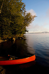 A canoe on shore in Lily Bay on Moosehead Lake Maine USA