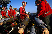 Red shirted ordnance men prepare to fit smart bombs and missiles to an F/A-18 fighter jet on deck of USS Harry S Truman. The Truman is the largest and newest of the US Navy's fleet of new generation carriers, a 97,000 ton floating city with a crew of 5,137, 650 are women.