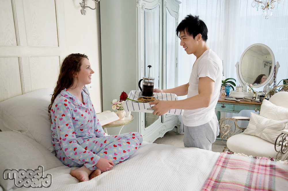Man bringing wife breakfast in bed