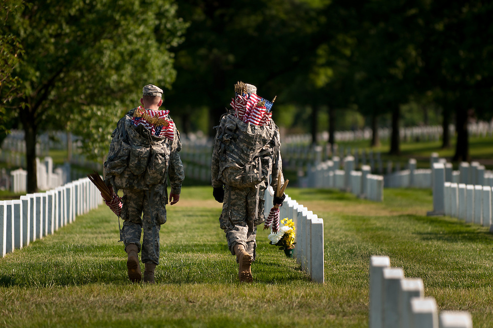 """Members of the 3rd U.S. Infantry, known as The Old Guard, place American flags before gravestones and niches of service members buried at Arlington National Cemetery in advance of the Memorial Day weekend. The tradition, known as """"flags in,"""" is conducted annually since 1948. Every available soldier in the 3rd U.S. Infantry participates, placing small American flags one foot in front and centered before more than 260,000 gravestones and about 7,300 niches at the cemetery's columbarium. Old Guard soldiers remain in the cemetery throughout the weekend, ensuring that a flag remains at each gravestone."""