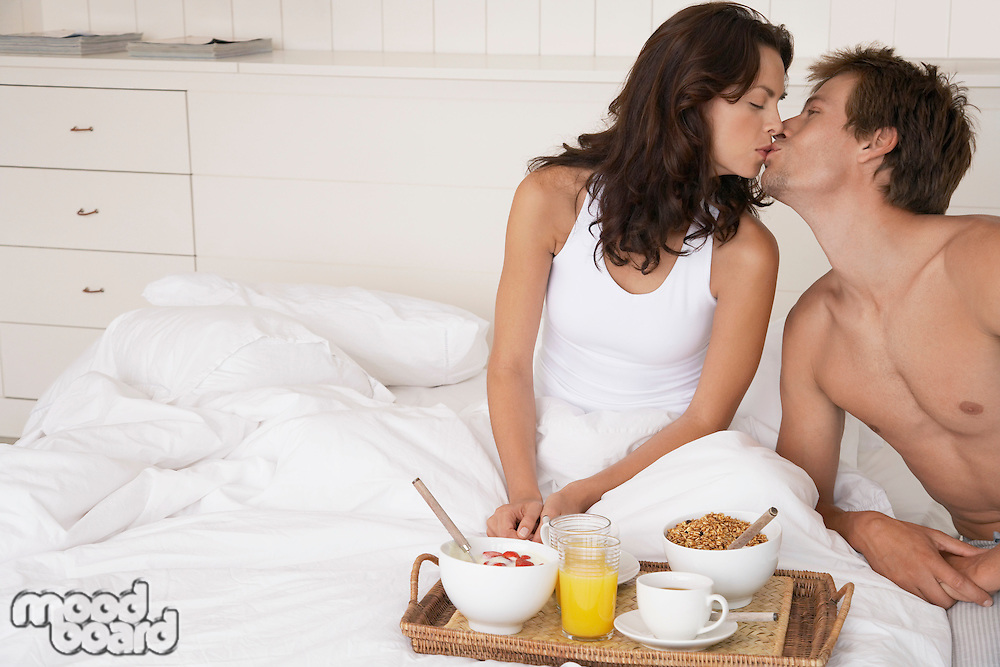 Couple kissing and having breakfast in bed