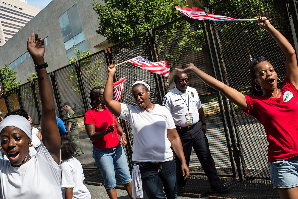 A Labor Day parade and march passes near the security fence for the Democratic National Convention on Monday, September 3, 2012 in Charlotte, NC.