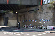 Following the attack on a group of Muslim men outside the Finsbury Park mosque which killed one person and seriously injured another ten, a Met Police officer looks at flowers leaft under the railway Bridge opposite the Islamic building, on 19th June 2017, in the borough of Islington, north London, England.