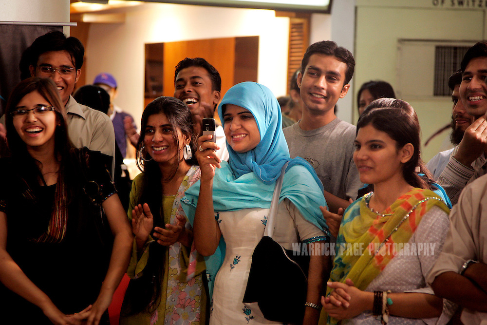 KARACHI, PAKISTAN - APRIL 19: Young Pakistanis take pictures and capture video on their mobiles of a live MTV Pakistan broadcast at the Park Towers shopping mall on April 19, 2008, in Karachi, Pakistan. According to reports, Telenor now has 50 million subscribers in Asia, accounting for 30% of Telenor's $17 billion annual revenue. Telenor is the third largest mobile operator in Pakistan's with nearly a fifth of the country's market and sales almost tripling in 2007 to $632 million. With fewer than 50% of Pakistanis owning a cell phone, international mobile companies are scrambling for a share of Asia's mobile markets. (Photo by Warrick Page)