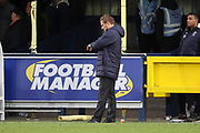 AFC Wimbledon manager Neal Ardley looking at his watch during the EFL Sky Bet League 1 match between AFC Wimbledon and Luton Town at the Cherry Red Records Stadium, Kingston, England on 27 October 2018.