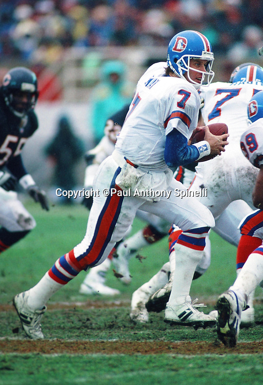 Denver Broncos quarterback John Elway (7) looks to hand off the ball on a running play during the NFL football game against the Chicago Bears on Dec. 18, 1993 in Chicago. The Broncos won the game 13-3. (©Paul Anthony Spinelli)