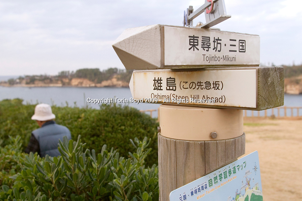 Nov. 27, 2009, Sakai City, Japan: Directional sign near spot where many suicides occur at the rocky cliffs of Tojinbo, a popular tourist attraction on the Japan Sea coast that's also known for the number of suicide deaths that occur here. Located in Sakai City, Fukui Prefecture, this scenic area known for it's coastal beauty, seafood and onsen hot springs resorts now adds suicide as a reason to come here. In 2008 twenty suicides occurred here, but this figure varies between Sakai City officials and a suicide help group dedicated to preventing suicides here. Called Kokoro ni Hibiku Bunshu Henshukyoku, this NPO founded in 2004 by retired policeman Yukio Shige (seen in this photo), who along with a group of volunteers patrols the cliffs on a daily basis to deter those contemplating jumping to their deaths. According to Shige, age 65, in the past five years since he founded his NPO, he is responsible for talking 222 people out of killing themselves. But even with Shige's efforts, the deaths here continue and as of late November, 2009, the current number of annual suicides at Tojinbo stands at thirteen. Japan has one of the highest suicide rates in the world and 2009 may surpass the record 34,427 deaths that occurred here in 2003. This increase is though to be a result of the Japanese recession which has been worsened by the global economic downturn. Depression is the number one cause for suicide in Japan, followed by illness and debt. Photo by Torin Boyd.