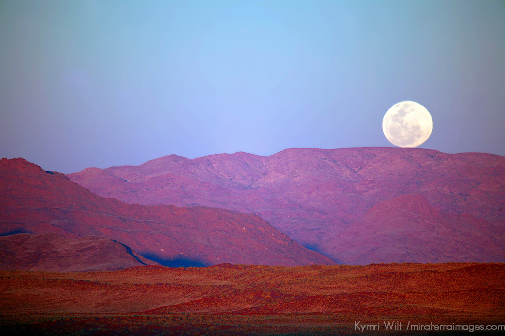 Africa, Namibia, Sossusvlei. A full moon rests on the crest of foothills in the NamibRand Nature Reserve, Namibia.