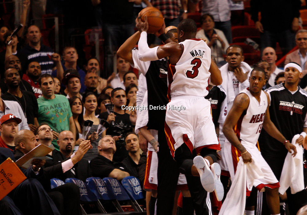 March 3, 2011; Miami, FL, USA; Miami Heat shooting guard Dwyane Wade (3) dives over the bench and into the fans while trying to save a loose ball during the fourth quarter against the Orlando Magic at the American Airlines Arena. The Magic defeated the Heat 99-96.    Mandatory Credit: Derick E. Hingle