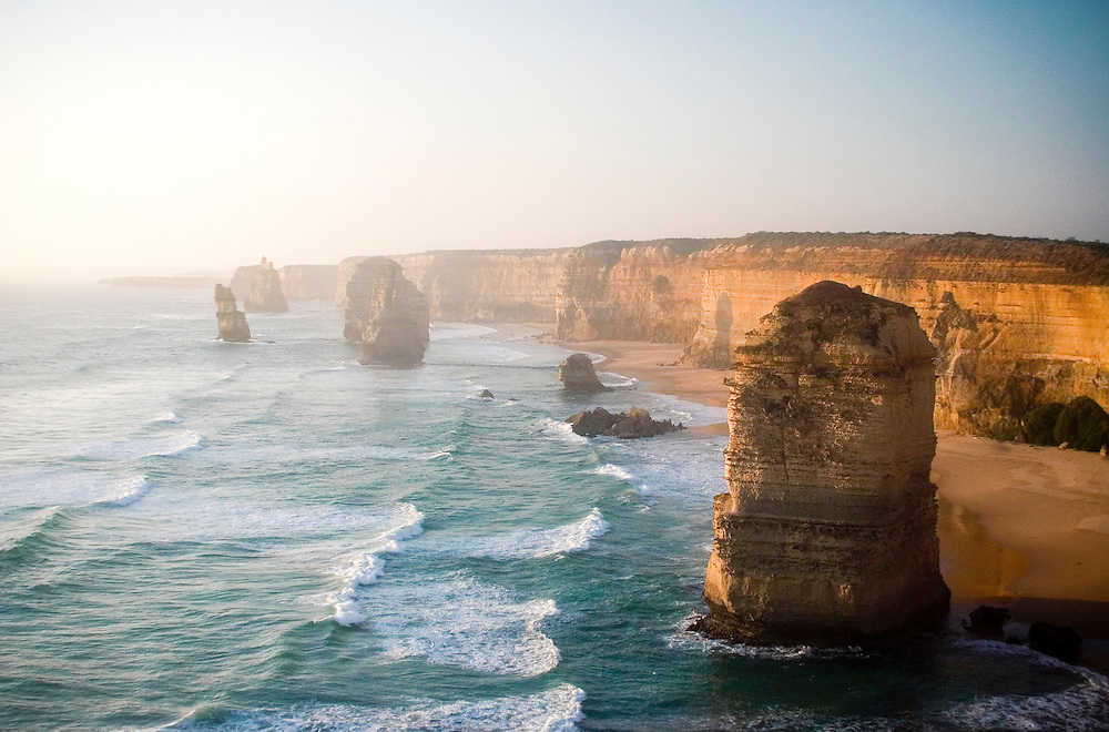 The Twelve Apostles rock formations stand in the setting sun.