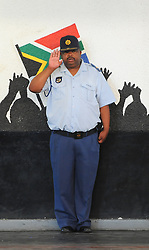 The City of Cape Town hosted an Evening of Remembrance at the OR Tambo hall, Khayelitsha. for the late former President of South Africa, Nelson Mandela. A police officer salutes during the playing of the national anthem, South Africa  Monday, 9th December 2013. Picture by Roger Sedres / i-Images
