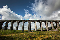 © Licensed to London News Pictures. 26/08/2015. Ribblehead, UK. A diesel train crosses the Ribblehead Viaduct after what was a gloomy start the cloud cover has broken in the Yorkshire Dales. Photo credit: Andrew McCaren/LNP