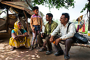 21st March 2014, Shakarpur, New Delhi, India. Rajesh Kumar Sharma (white shirt) talks with Ravi Kumari (9) and his family at their home on the Yamuna Bank during a home visit, with father Mr Baldev Saika (40, centre) and mother Bhuri (left), Sharkarpur, New Delhi, India on the 21st March 2014.<br /> <br /> Ravi is a regular pupil at a makeshift school under a metro bridge near the Yamuna Bank Metro station in Shakarpur. Rajesh Kumar Sharma (born 01/02/1970), started this makeshift school in 2011. Six mornings a week he teaches underprivileged children for three hours while his younger brother replaces him at his general store in Shakarpur. His students are children of labourers, rickshaw-pullers and farm workers. This is the 3rd site he has used to teach under privileged children in the city, he began in 1997. <br /> <br /> PHOTOGRAPH BY AND COPYRIGHT OF SIMON DE TREY-WHITE<br /> + 91 98103 99809<br /> email: simon@simondetreywhite.com<br /> photographer in delhi<br /> journalist