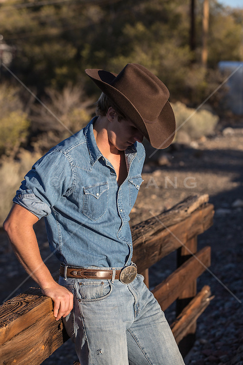 cowboy leaning on a wooden fence with his head lowered