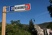 The signpost for the local Gendarmerie in blue skies, on 23rd May, 2017, in Lagrasse, Languedoc-Rousillon, south of France. Lagrasse is listed as one of France's most beautiful villages and lies on the famous Route 20 wine route in the Basses-Corbieres region dating to the 13th century.