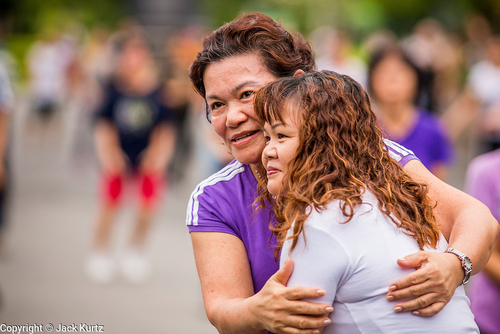 06 OCTOBER 2012 - BANGKOK, THAILAND: Women hug during an exercise class in Lumphini Park in Bangkok. Lumphini Park is 142 acre (57.6-hectare) park in Bangkok, Thailand. This park offers rare open public space, trees and playgrounds in the congested Thai capital. It contains an artificial lake where visitors can rent boats. Exercise classes and exercise clubs meet in the park for early morning workouts and paths around the park totalling approximately 1.55 miles (2.5km) in length are a popular area for joggers. Cycling is only permitted during the day between the times of 5am to 3pm. Smoking is banned throughout smoking ban the park. The park was created in the 1920's and named after Lumbini, the birthplace of the Buddha in Nepal.   PHOTO BY JACK KURTZ