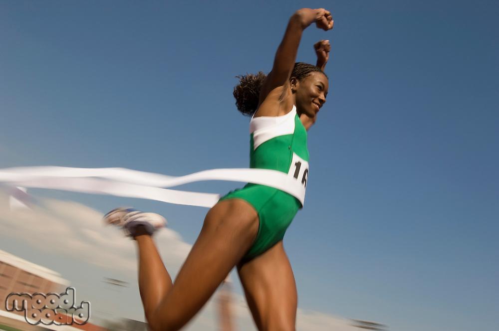 Female track athlete crossing finishing line
