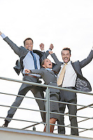 Low angle view of excited businesspeople with arms raised standing on terrace against clear sky