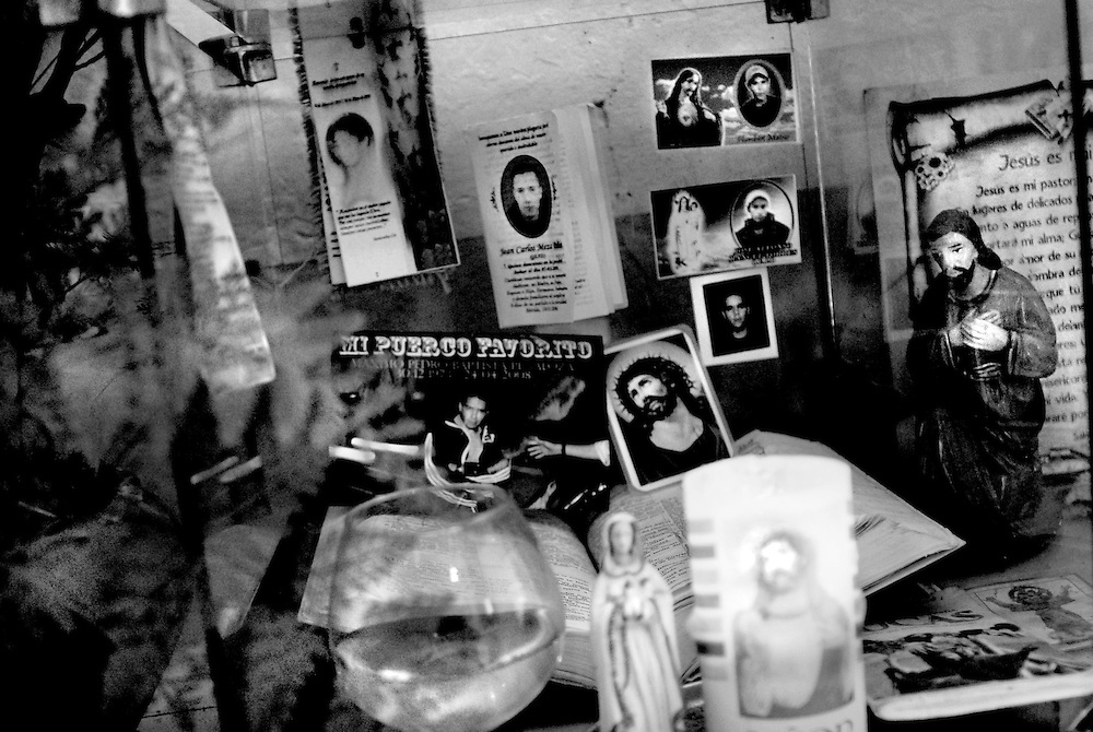 A family's religious shrine to murdered friends and family members, adorned with holy water, candles, and 'recuerdos' wallet-sized photos of the deceased accompanied by religious graphics and Catholic prayers, popular among families after they have lost someone. The six 'recuerdos' pictured in this image were all made for young men close to the family that were murdered in the past six months. The majority of men featured in this project keep upwards of a dozen 'recuerdos' of their fallen friends in their wallets. Some have had over 20 friends fatally shot within the past 2-3 years. The owner of this shrine, placed by his doorway, habitually kisses his finger and touches each photo before leaving his house, and asks his friends to protect him while he is in the street.