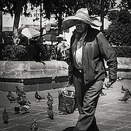 Man with sombrero and a bucket in hand walks at one of the squares in Zacatecas