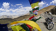 Tibetan prayer flags flutter violently in the wind as Suzanne Lee and Sanjit Das stop to take pictures as they ride through some of the World's Highest Motorable roads during their trip Across the Himalayas in the Valley of Ladakh, India, on Royal Enfield motorcycles in June 2014. A resulting 4 minute short film was made, all shot on an arsenal of Sony ActionCam video cameras. Photo by Suzanne Lee/Panos Pictures