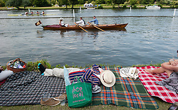 © London News Pictures. 05/07/2012.  Henley-on-Thames, UK. A A spectator sleeping on the banks of the river on day three of Henley Royal Regatta on the River Thames at Henley-on-Thames, Oxfordshire on July 03, 2013. The 5 day regatta over the first weekend in July, races head-to-head knock out competitions over a course of 1 mile between rowing teams from throughout the world. Photo credit: Ben Cawthra/LNP