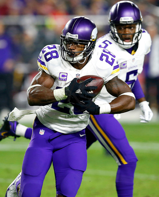 Minnesota Vikings running back Adrian Peterson (28) runs after the hand off from quarterback Teddy Bridgewater (5) during the first half of an NFL football game against the Arizona Cardinals, Thursday, Dec. 10, 2015, in Glendale, Ariz. (AP Photo/Rick Scuteri)