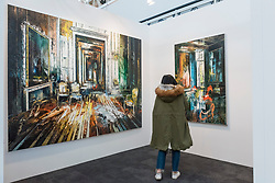 "© Licensed to London News Pictures. 16/01/2018. LONDON, UK. A visitor views ""The Blue Room"" and ""Set Piece"" by John Monks.  Preview day of the 30th anniversary of the London Art Fair.  The fair launches the international art calendar with modern and contemporary art from leading galleries around the world and is taking place at the Business Design Centre, Islington from 17 to 21 January 2018.   Photo credit: Stephen Chung/LNP"
