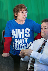 """© Licensed to London News Pictures . 12/05/2014 . Manchester , UK . A woman with an """" NHS not trident """" t-shirt in the audience as the leader of the Labour Party , Ed Miliband , delivers a speech on health at the National Squash Centre in Manchester today (Monday 12th May 2014) . Photo credit : Joel Goodman/LNP"""