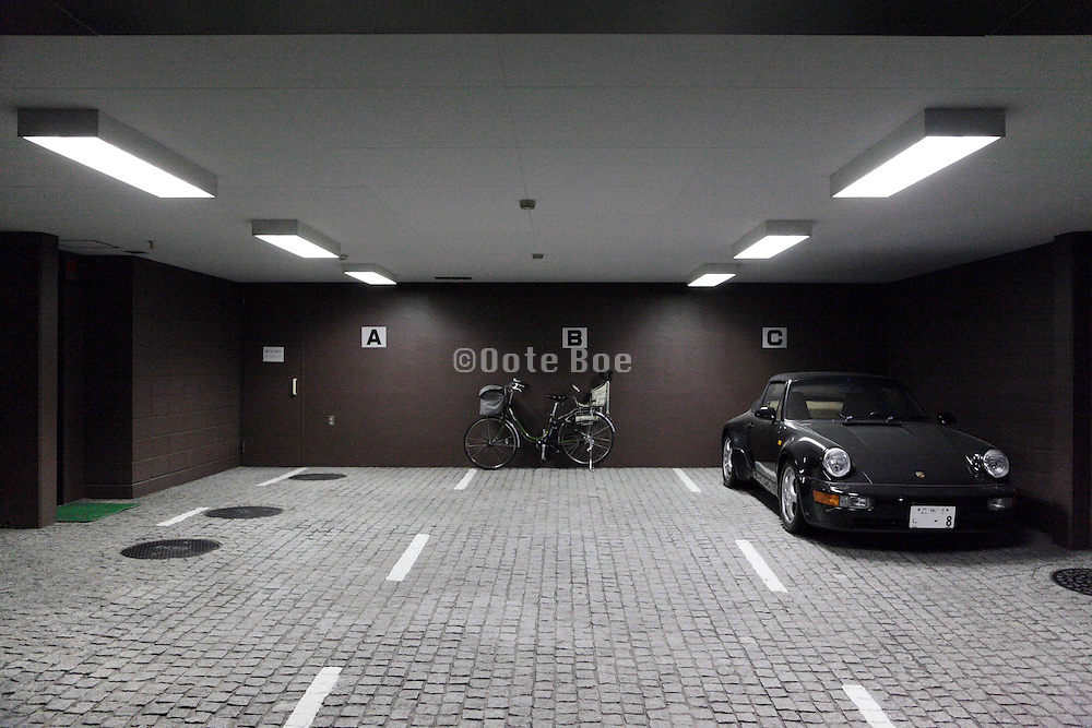 apartments ground floor parking garage with bicycle and a Porsche car covered with dust