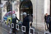 A lady pushes a child's buggy while carrying inflated party balloons past a bus stop in Kingston town centre, on 13th November 2019, in London, England.