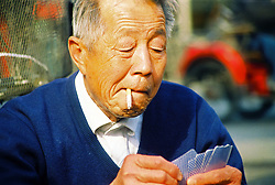 China, Beijing, 2008. Intent on his hand, a man ponders his next move in a neighborhood card game that drew many onlookers.